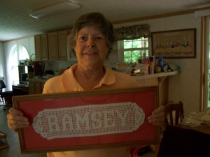 Millied Crawford shows name she crocheted and framed.